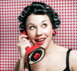 a 50s style housewife with hair rolls gossiping in a red vintage phone